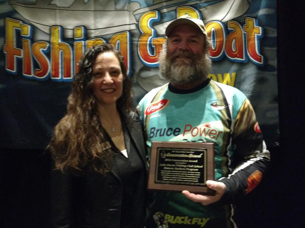 The Spring Fishing and Boat Show's Vita Pallotta congratulates Richard Elliott, organizer of the Lake Huron Fishing Club's School Salmon Hatchery Program, which earned the Conservation Project of the Year honour