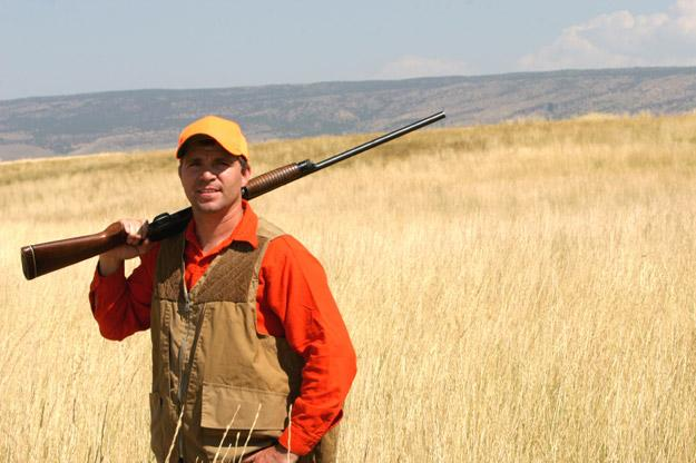 Hunter with a yellow hat and a rifle