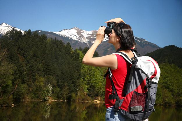 Photographer taking a photo of the mountains and trees