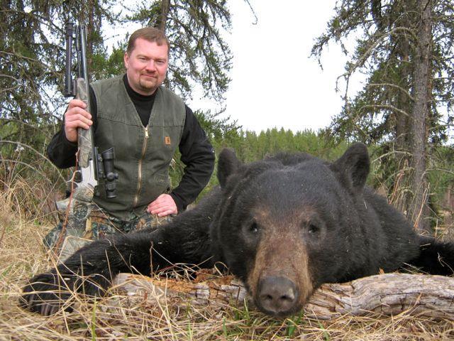 A hunter with his black bear kill