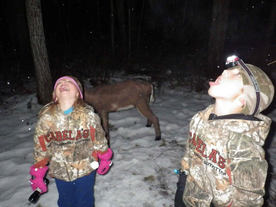 Kids catching snowflakes at night