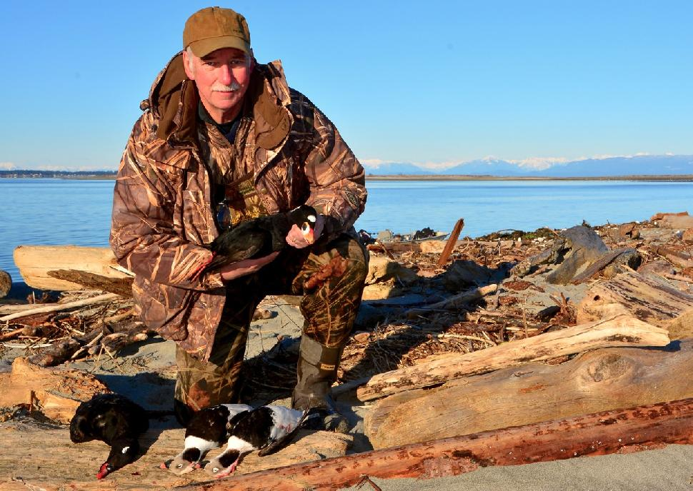 Credit: Ken Bailey The author holds a surf scoter; at his feet lie a white-winged scoter and two longtails